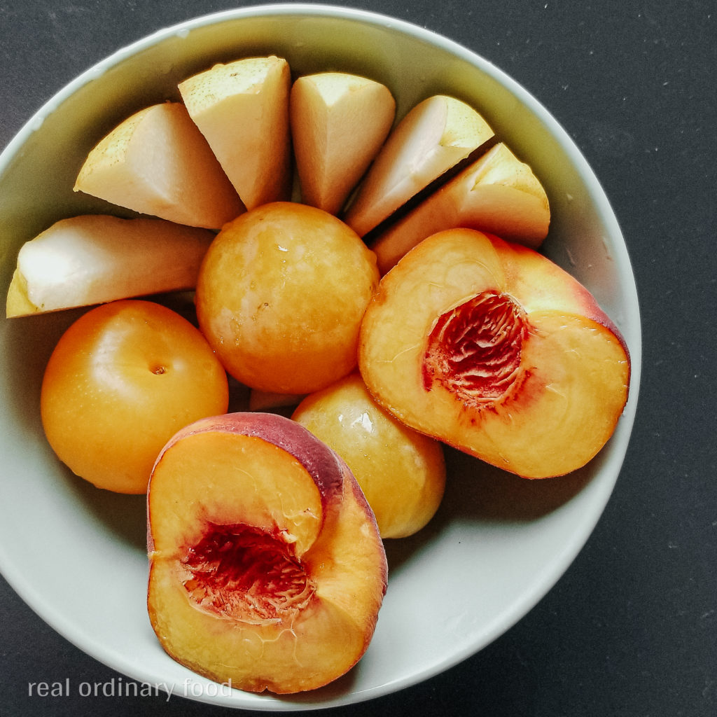 fruit bowl of pears, yellow plums, and yellow peaches