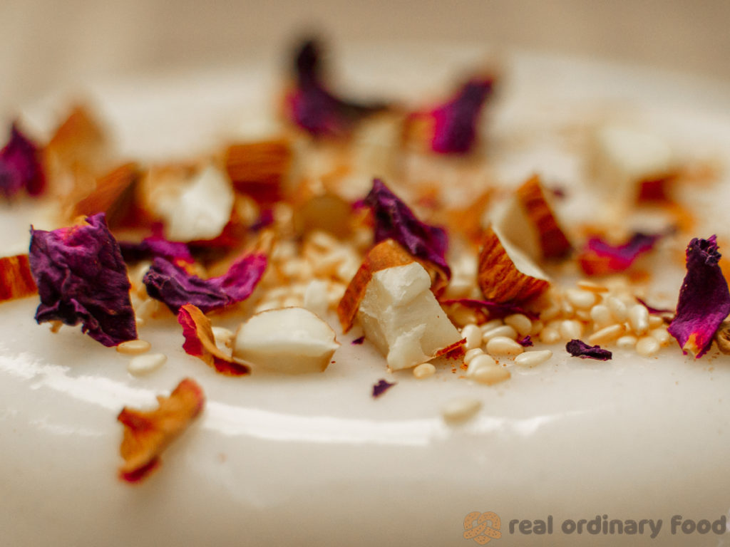 vegan muhallebi decorated with rose petals, sesame seeds, and chopped almonds
