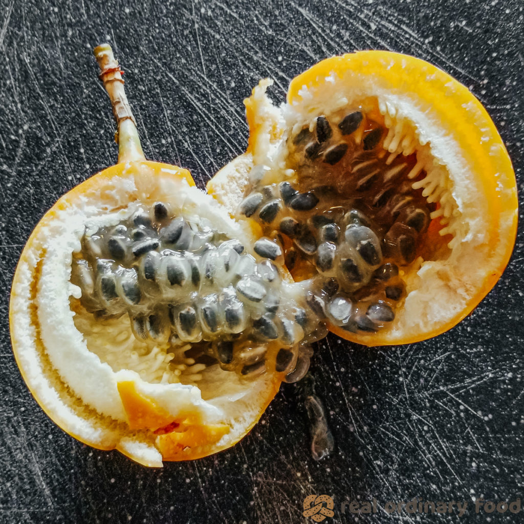 passion fruit cracked open on black cutting board