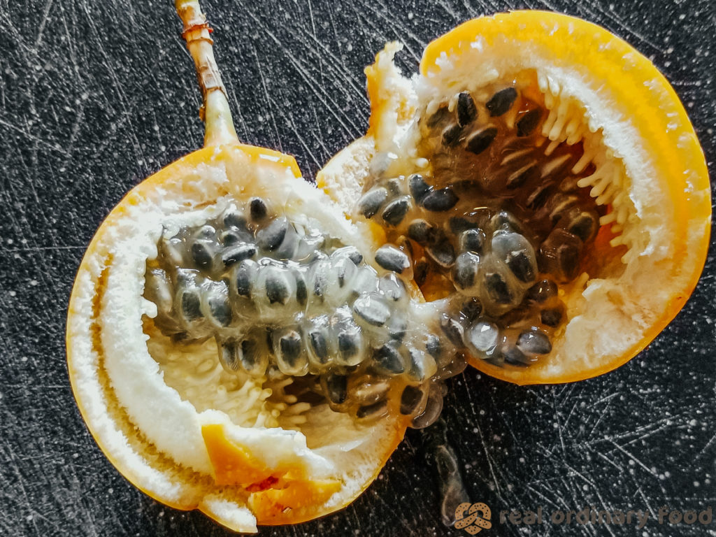 fresh passion fruit cracked open on black cutting board
