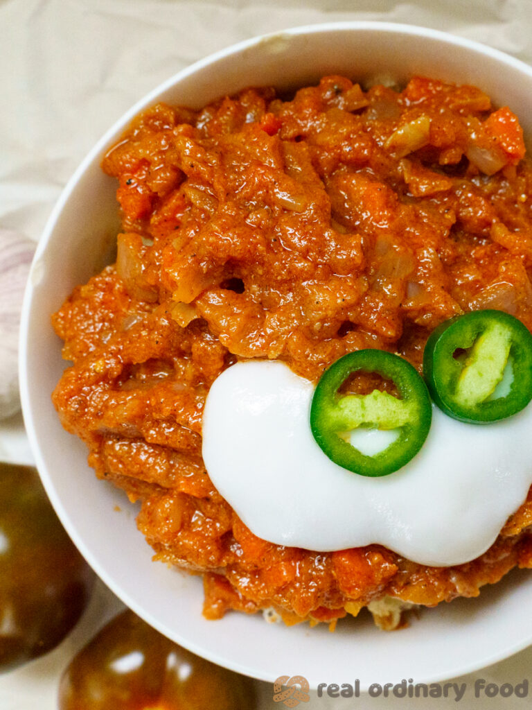 bowl of silsi eritrean tomato sauce topped with yogurt and jalapeno pepper