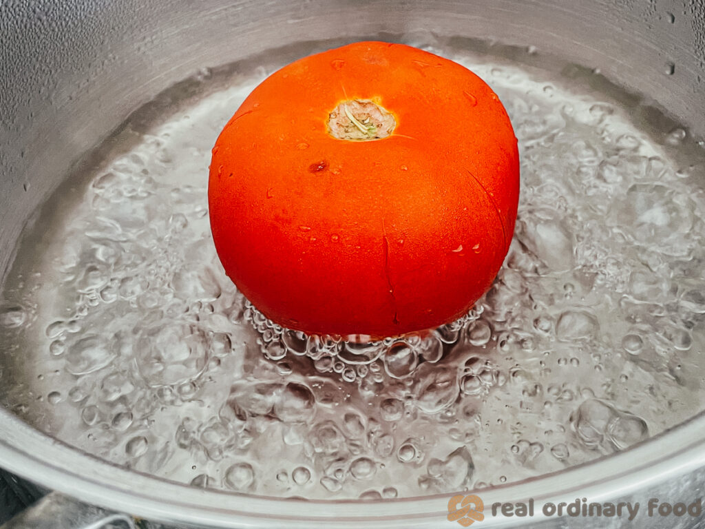 blanching a tomato in boiling water