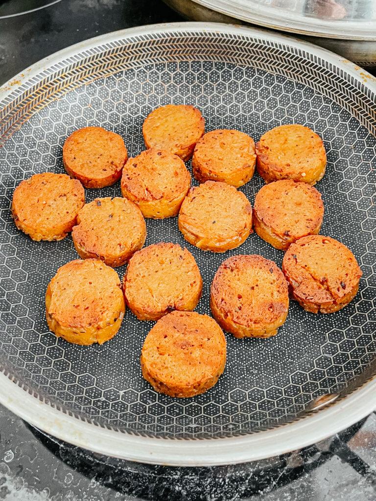 frying sliced vegan Andouille sausages in skillet